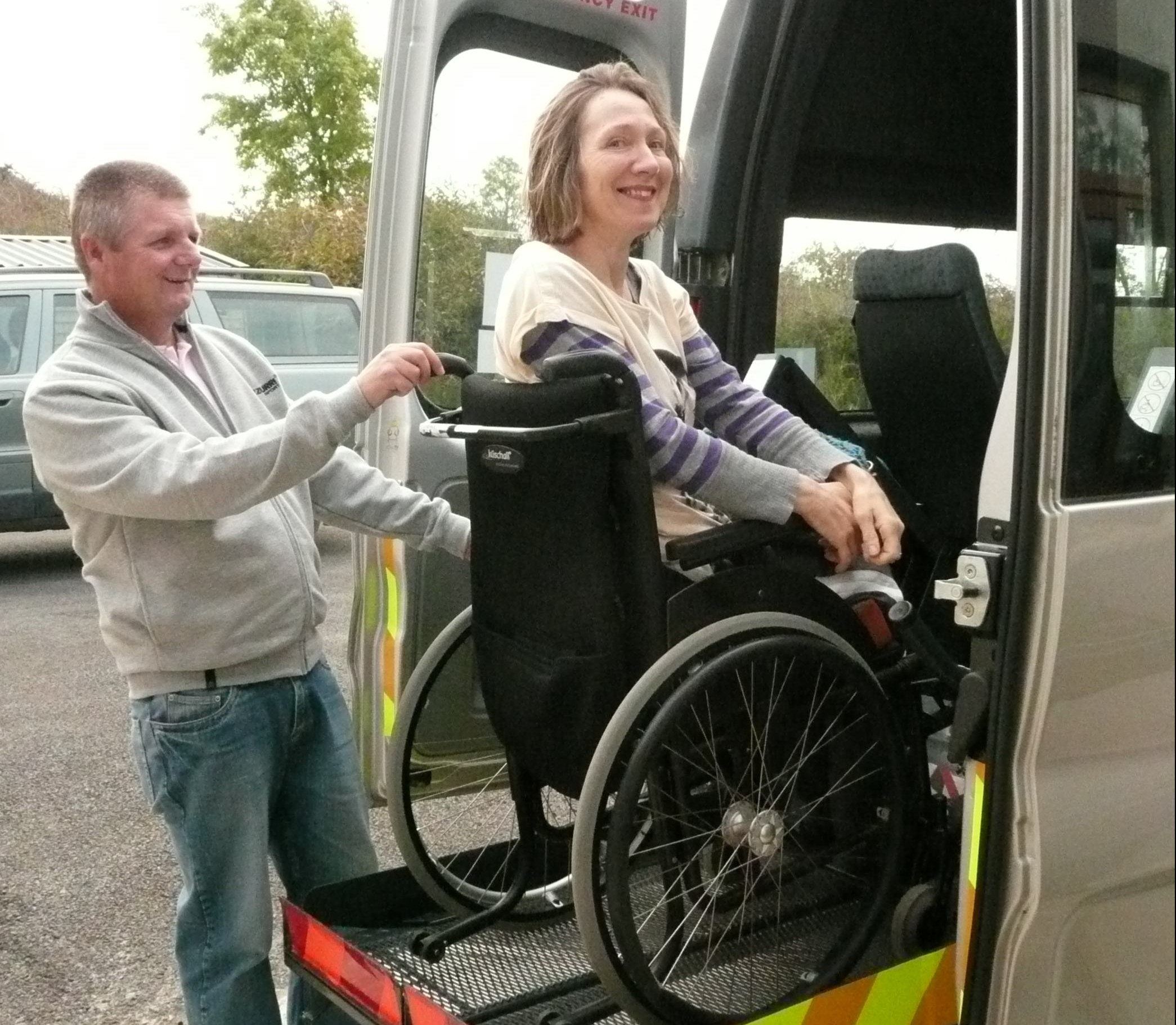 Personal Assistant assisting disabled person into accessible transport