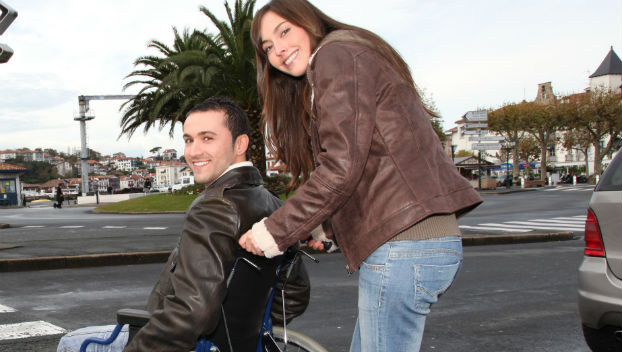 Personal assistant assisting wheelchair user